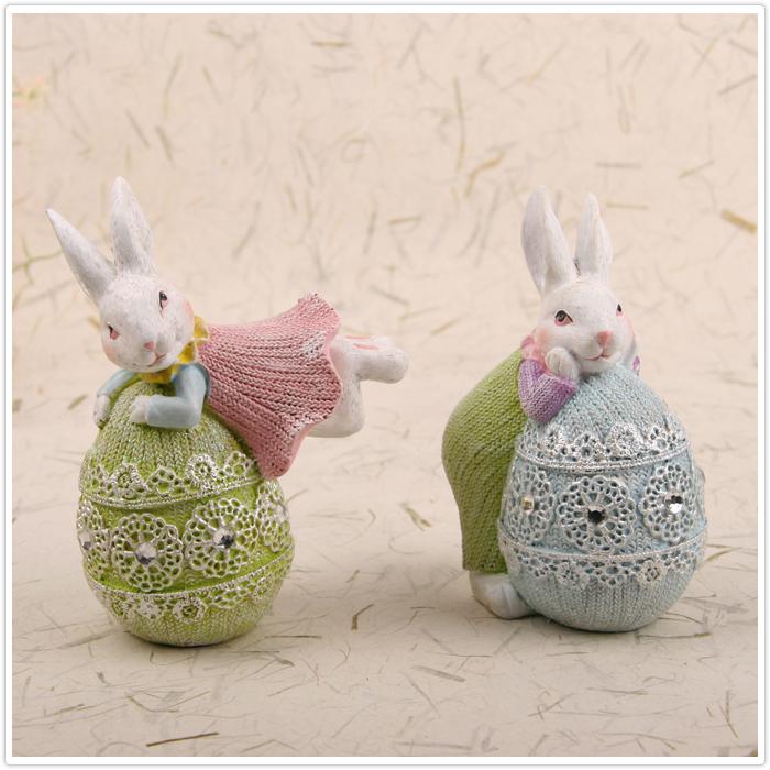 可爱的小兔子,一只穿着粉红色裙子趴在圆球上面,另外一直穿着浅绿色